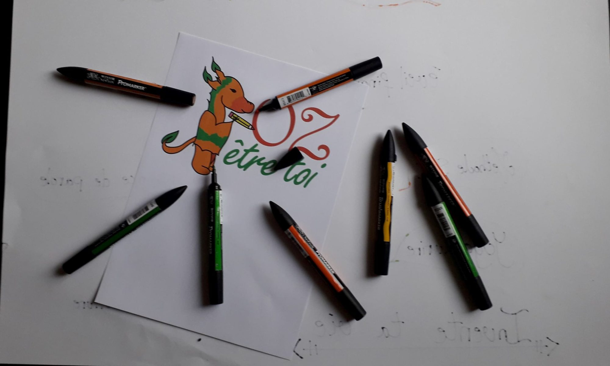 logo oz en couleur avec crayon de la meme couleur que le logo