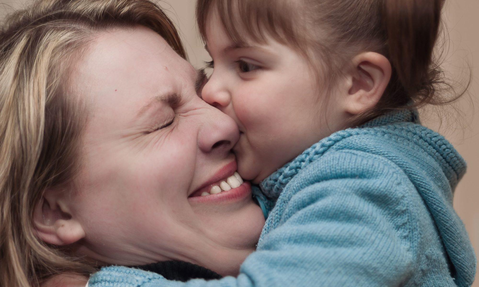 parentalité bienveillante, une fillette qui fait un gros bisous à sa maman qui en ferme les yeux